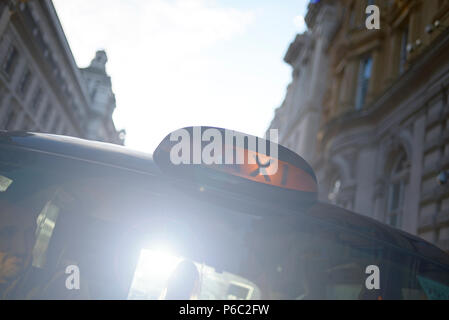 Close up of a London black cab in summer sunshine with flare on the lens - Stock Photo
