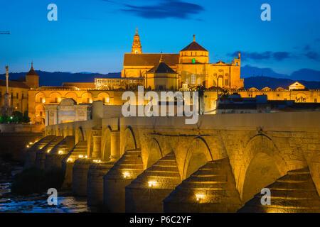 Cordoba bridge, view at night across the Roman bridge (Puente Romano) towards the Cathedral Mosque (La Mezquita) in historic Cordoba, Andalucia, Spain