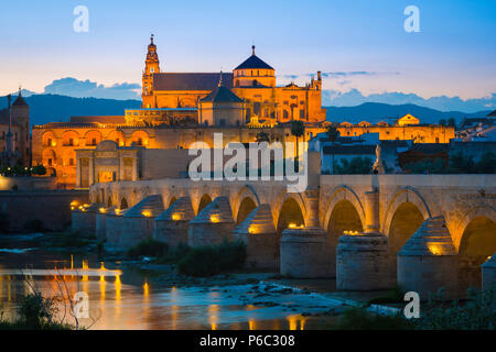 Andalucia Spain architecture, view at night across the Roman bridge on the Rio Guadalquivir towards the Cathedral and La Mezquita in Cordoba, Spain. - Stock Photo