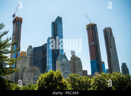 Skyscrapers constructed and under construction along the West 57th Street corridor in Midtown Manhattan in New York destined a shadows over Central Park, seen on Saturday, June 16, 2018. A recent study reported that the One57 and other proposed and under construction 'mega-towers' for the 'über-rich' over 1000 feet will cast long shadows at certain times of the year plunging parts of the southern section of the landmark Central Park in shadow. The buildings achieve their height by purchasing the air rights of smaller buildings. (© Richard B. Levine) - Stock Photo