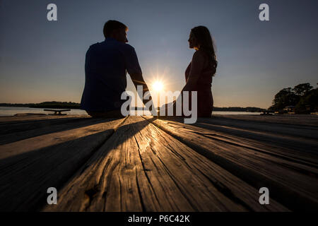 A young couple spends the evening watching the sunset from a dock in southeast Georgia. - Stock Photo