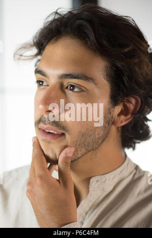 Close Up of Young Man Touching His Chin - Stock Photo