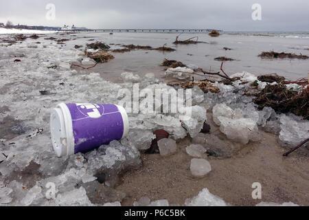 Ahlbeck, Germany, Empty coffee mug lying on the beach in the ice - Stock Photo
