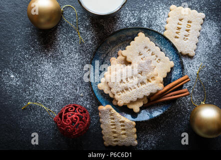 Homemade honey and cinnamon biscuits decorated with Christmas stamps - Stock Photo
