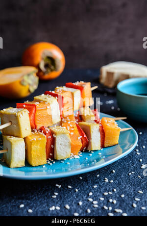 Vegetarian skewers with persimmons, Tofu cheese, red pepper, sesame seeds and served with soya sauce - Stock Photo
