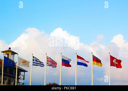 Flags of different countries flapping in wind against blue sky - Stock Photo