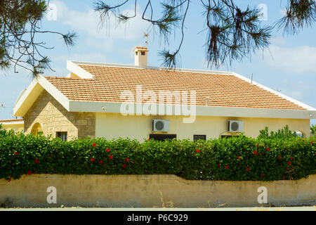 View of house with orange roof behind fence through tree branches against blue sky - Stock Photo