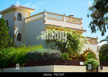 Part of house with terrace wreathed in flowering shrub Bougainvillea with white flowers against blue sky - Stock Photo