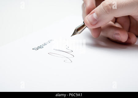 pen in the man's hand and signature on a white - Stock Photo