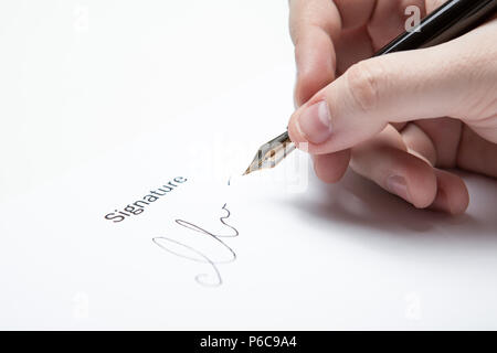 pen in the man's hand and signature on a white closeup - Stock Photo