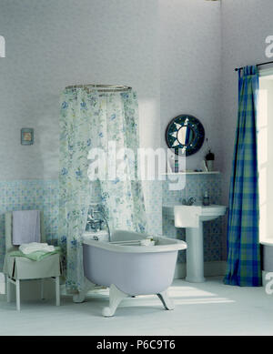 White rolltop bath with floral shower curtain in centre of white bathroom with blue checked curtains and white flooring - Stock Photo