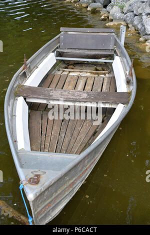 old rowing fishing and bathing boats in a lake in bavaria, neglected old and rotten row boat made of metal and wood - Stock Photo