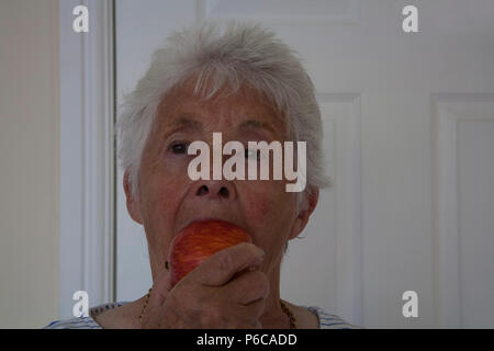Elderly woman enjoying eating a Royal Gala apple eating one of recommended five a day - Stock Photo