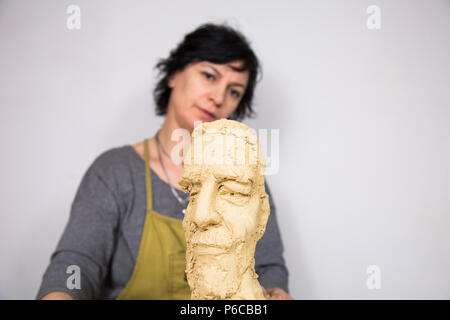 Sculptor artist creating a bust sculpture with clay. She is happy of her work, she is concentrated, she is sculpting a woman. - Stock Photo