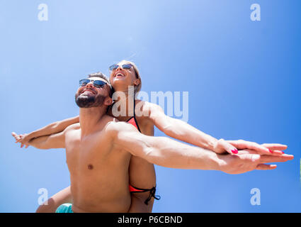 Man carrying woman piggyback on beach. - Stock Photo