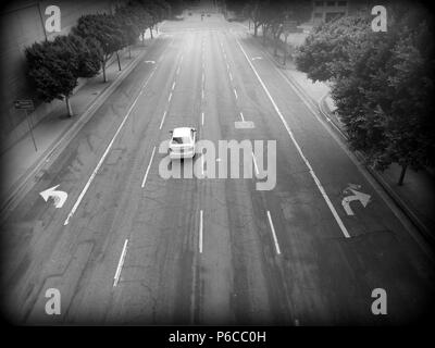 A quiet morning in Los Angeles; one car cruises a multi-laned road - Stock Photo