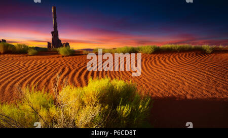 Spectacular sunrise over rock formations and sand dunes in Monument Valley, Arizona - Stock Photo