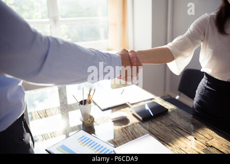 Close-up Of Two Business Partners Shaking Hands Over Desk In Office - Stock Photo