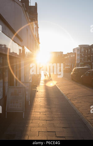 Ring of light shining on pavement through a road down a London street at Sunset as people go about their daily life, Hackney, England, Great Britain. - Stock Photo
