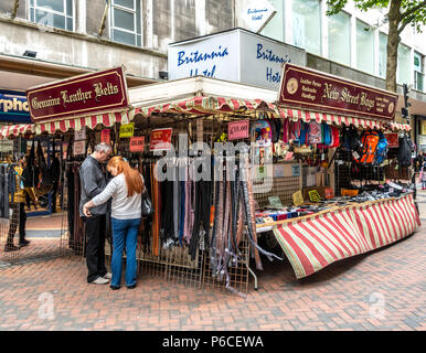 Customers examining leather belts at the New Street Bags trading stall in Mew Street, Birmingham City Centre, West Midlands, England, UK - Stock Photo
