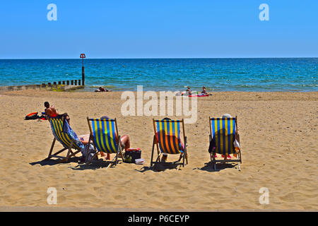 'Oh we do like to be beside the seaside!' People relaxing and enjoying the summer sunshine on the sandy beach between Boscombe and Bournemouth - Stock Photo