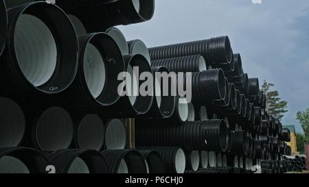 Warehouse of finished plastic pipes industrial outdoors storage site. Manufacture of plastic water pipes factory. Process of making plastic tubes on t - Stock Photo