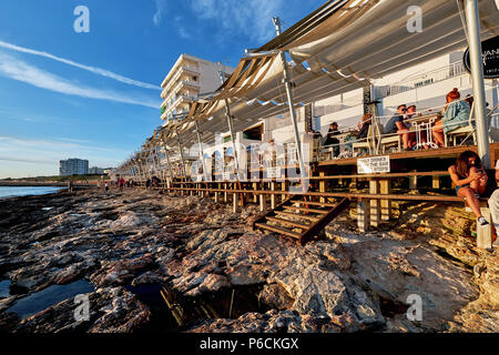 Ibiza Island, Spain - May 1, 2018: Crowds of people meet the sunset at the seafront terrace of Cafe Del Mar. This place is famous for views to the sun - Stock Photo