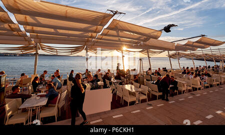 Ibiza Island, Spain - May 1, 2018: Crowds of people meet the sunset at the seafront terrace of Savannah cafe, located on the West Coast of Ibiza. This - Stock Photo