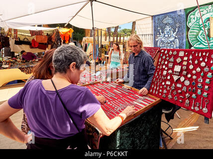 Ibiza Island, Spain - May 2, 2018: Seller and buyers at the Hippy market of Ibiza Island. Stall selling fashion accessories and silver jewellery with  - Stock Photo