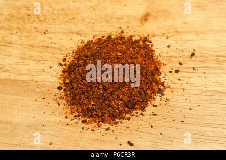 A pile of dried crushed coarse ground red hot pepper chilli flakes and seeds spice powder closeup on wooden board - Stock Photo