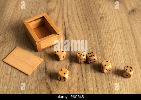 Wooden round corner dice six sided dots set for playing with box on wooden board surface as background - Stock Photo