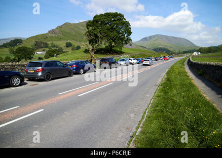 hill walkers cars parked in layby on the a591 road near fields and hills near grasmere in the lake district cumbria england uk - Stock Photo