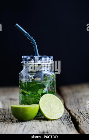 Citrus fruit and herbs infused sassi water for detox or dieting in glass bottles on wooden board, dark background. - Stock Photo
