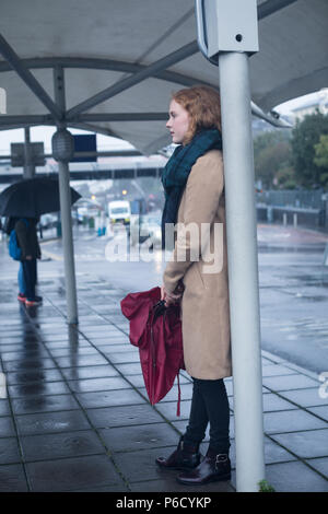 Young woman holding an umbrella standing at bus stop - Stock Photo