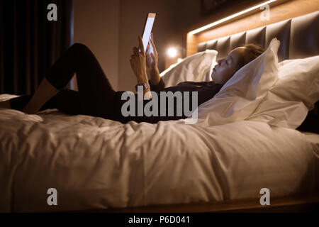 Woman using digital tablet while relaxing on bed - Stock Photo