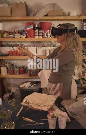 Female potter using virtual reality headset - Stock Photo