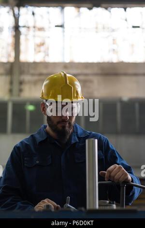 Technician in protective workwear cutting metal - Stock Photo