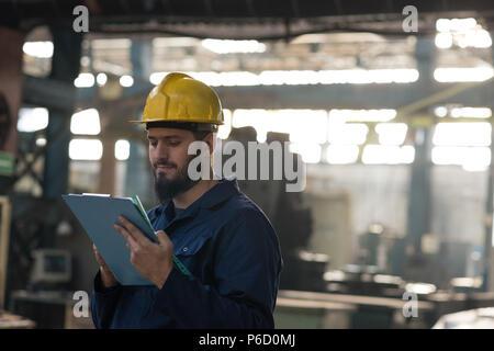Technician maintaining record on clipboard - Stock Photo