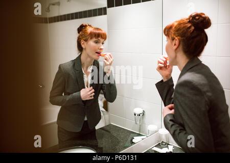 Businesswoman applying lipstick in bathroom - Stock Photo