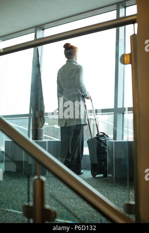 Businesswoman standing with luggage in hotel room - Stock Photo