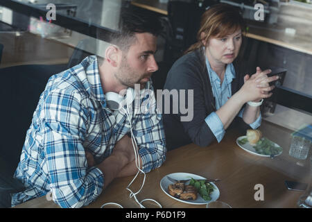 Business colleagues sitting in cafeteria - Stock Photo
