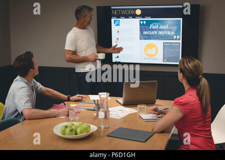 Businessman giving presentation to colleagues in meeting room - Stock Photo