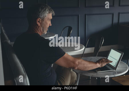 Businessman using laptop in cafeteria - Stock Photo