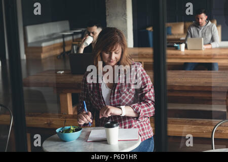 Businesswoman writing on a diary in cafeteria - Stock Photo