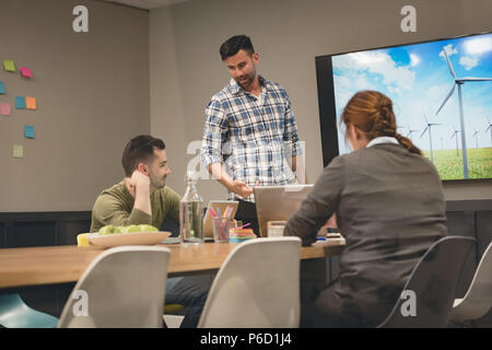 Business colleagues interacting with each other in meeting room - Stock Photo