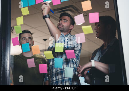 Business colleagues writing on sticky note - Stock Photo