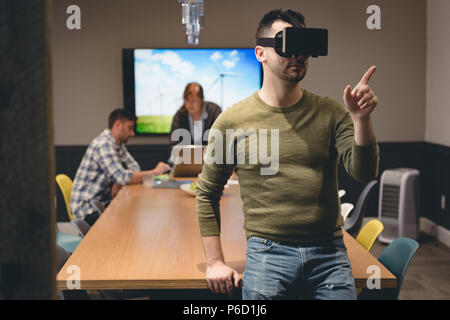 Businessman using virtual reality headset in meeting room - Stock Photo