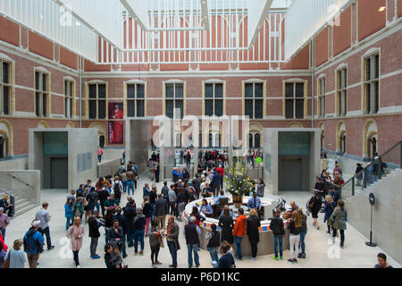 Amsterdam, Netherlands - May 2018: Visitors in modern main hall in the new atrium of the Rijksmuseum. Entrance to museum, massive ceiling decorations and people in dutch national museum. - Stock Photo