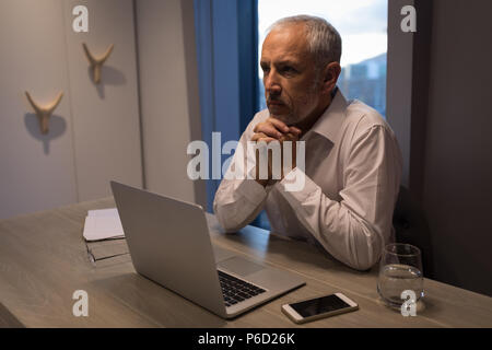 Businessman thinking deeply while sitting at desk