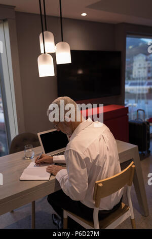 Businessman taking notes on a notebook - Stock Photo